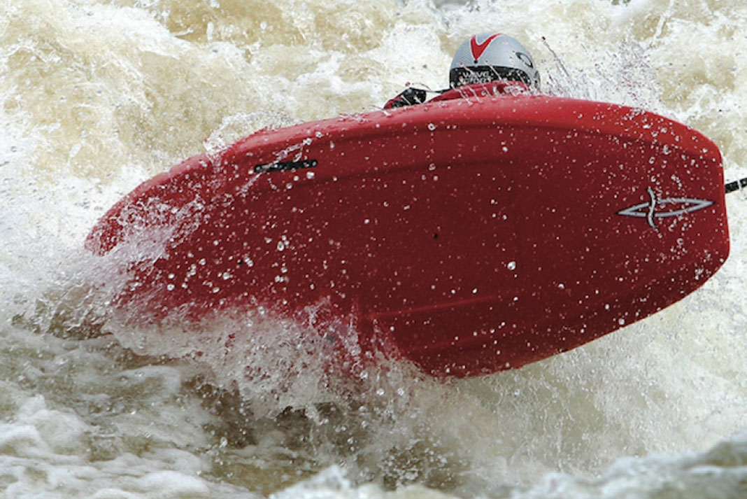 Paddler catches some air in a Pyranha Kingpin Icon whitewater kayak
