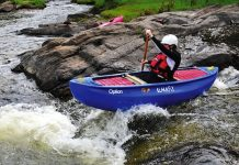 Person paddles the Blackfly Option canoe through a set of rapids