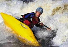 Man paddles a Titan Genesis freestyle kayak through whitewater rapids