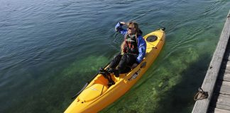 Woman floats on clear water in the Hobie Mirage Revolution 13 kayak