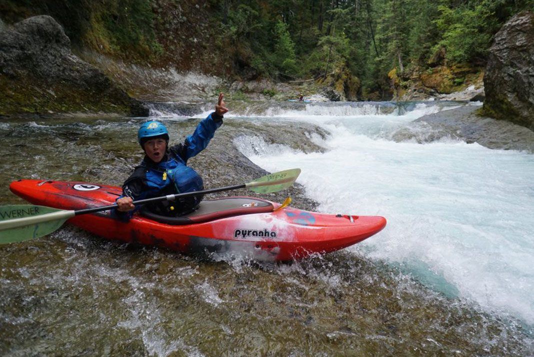 Woman in whitewater kayak, with arm raised in air