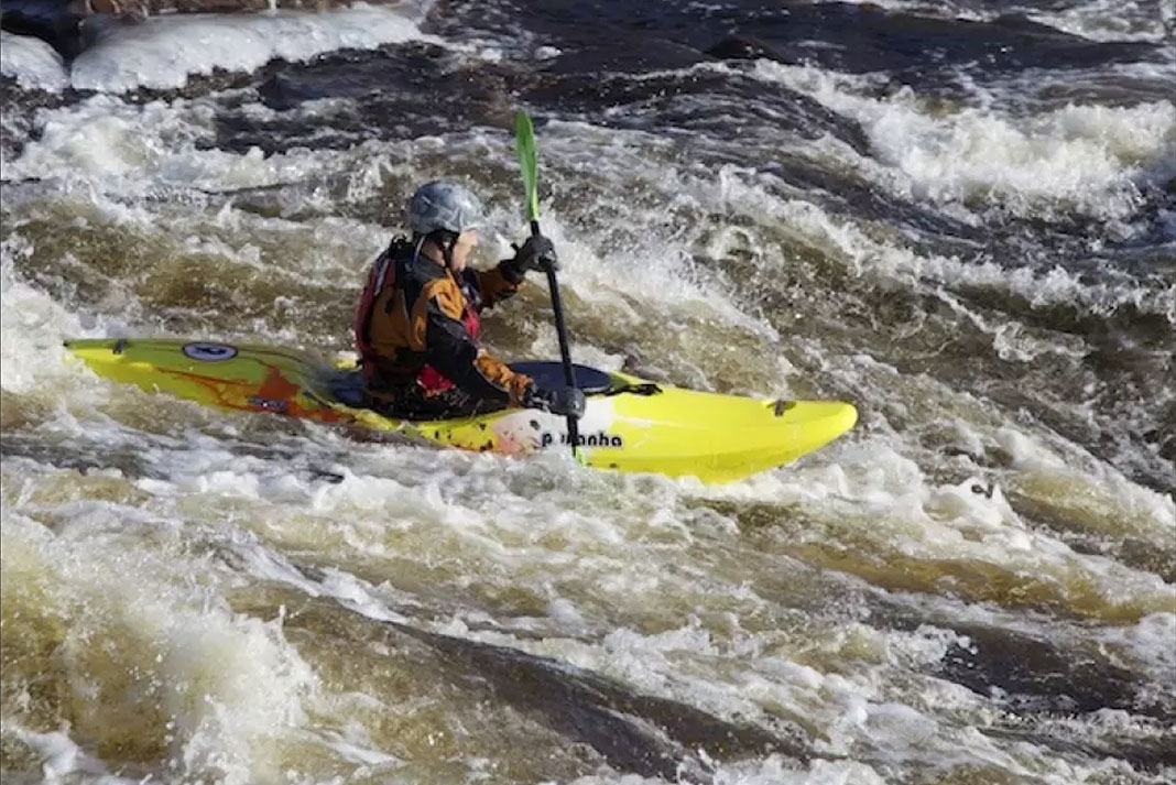 A person kayaking through whitewater in the Pyranha 9R