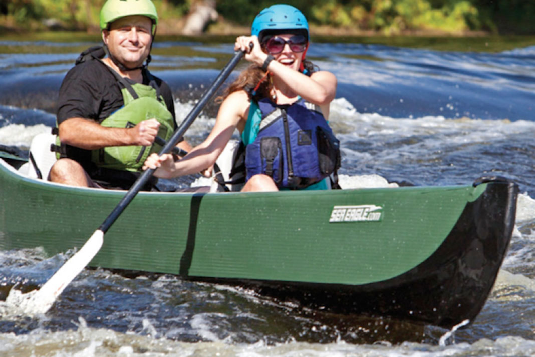Two people riding in the inflatable Sea Eagle Travel Canoe 16