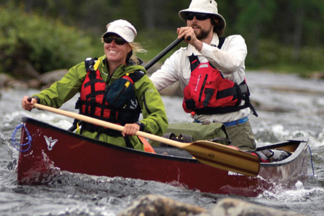 Man and woman paddle in the Nova Craft Prospector 17 TuffStuff Expedition canoe