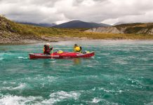 Two people paddle through turquoise water in the Pakboats PakCanoe 170