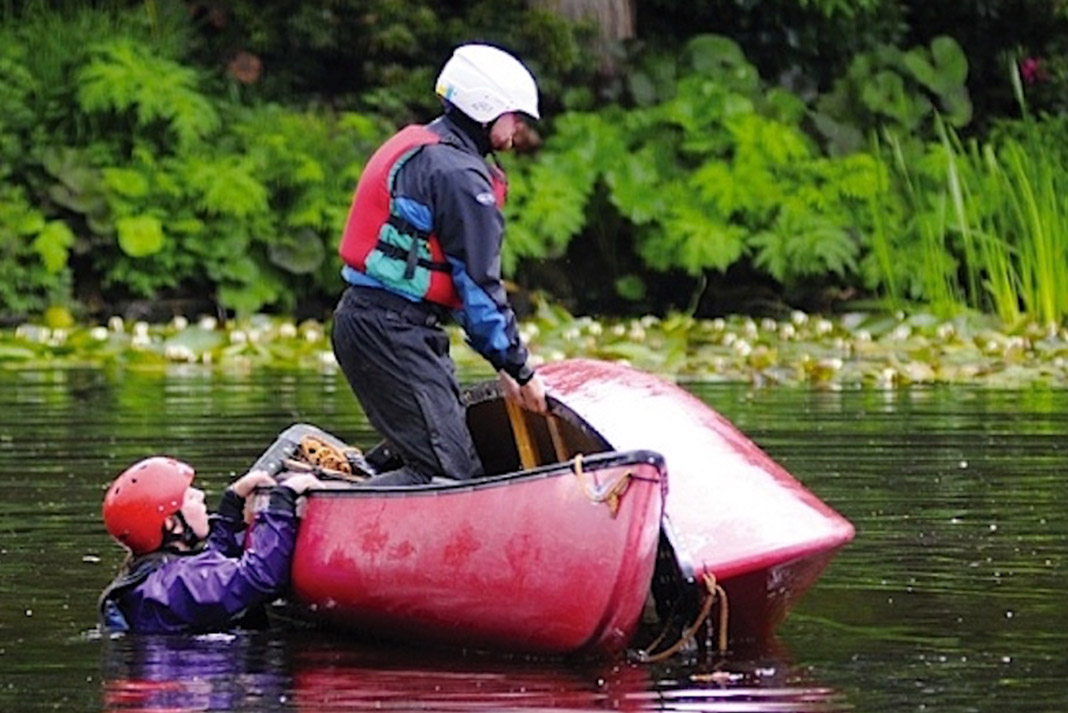 One person standing in canoe lifting a swamped canoe, another person holding the gunwales of the stable canoe.