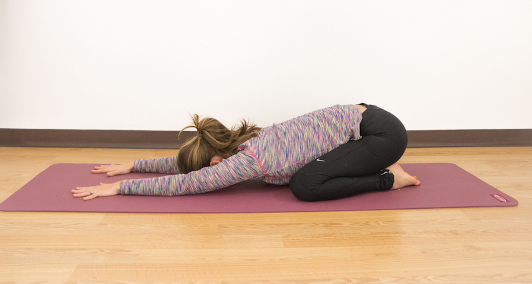 Woman doing child's pose on a yoga mat
