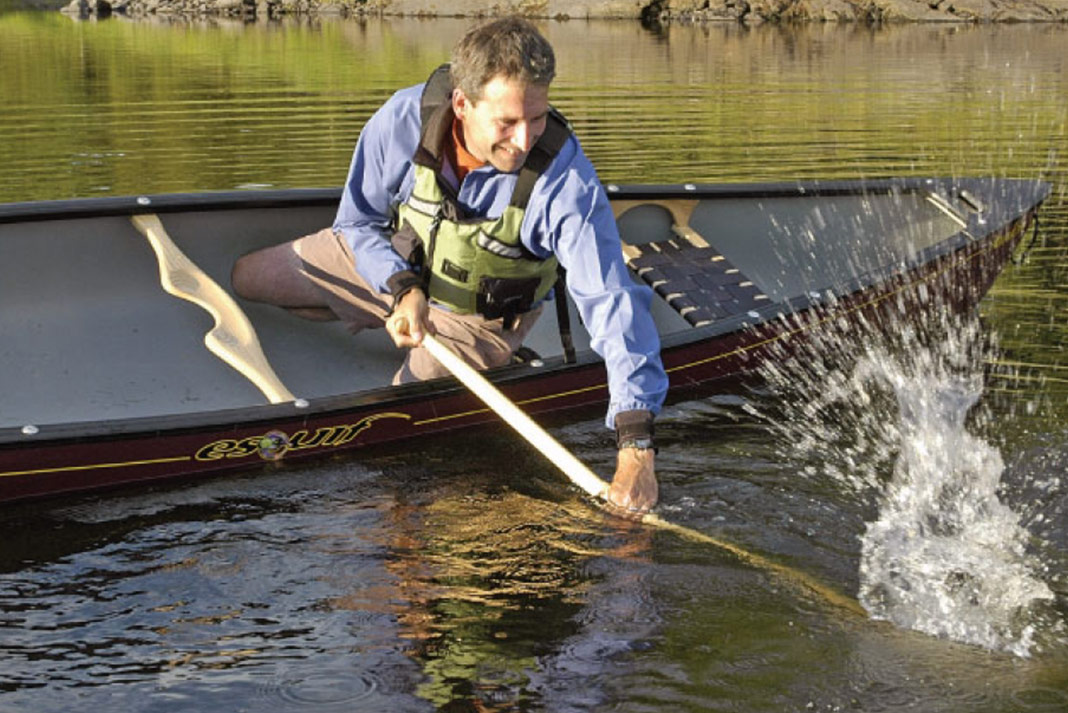 Man performing low bace in canoe