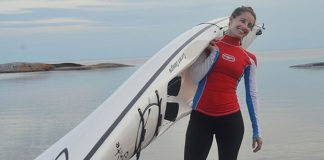 Woman standing and carrying a Current Designs Ignite kayak