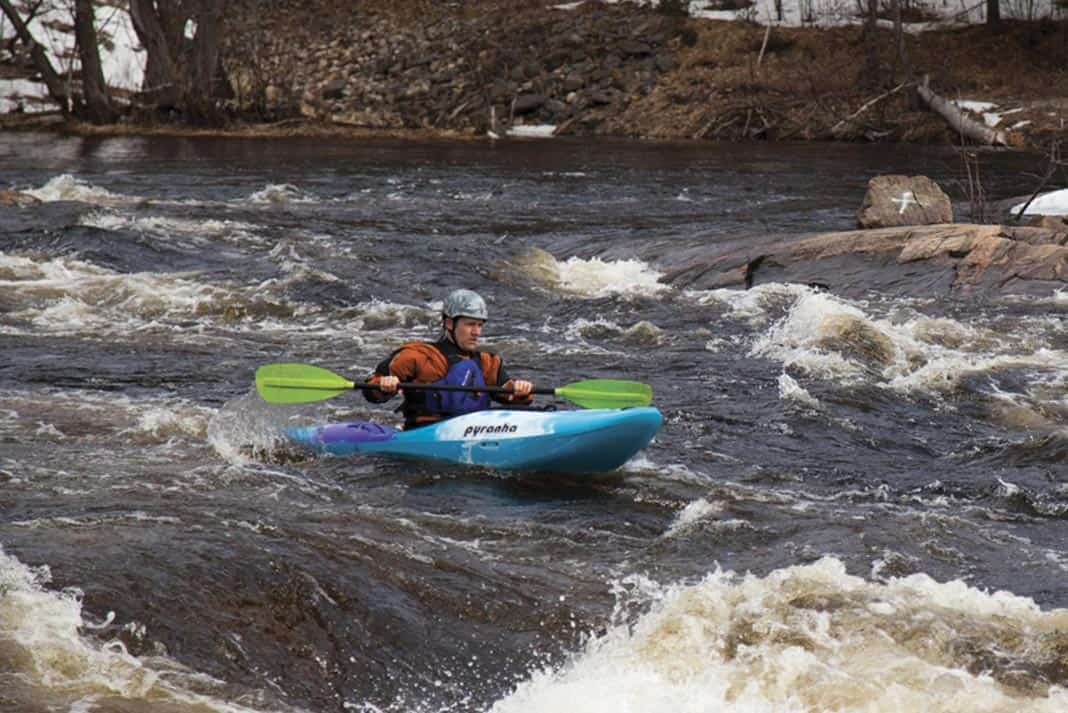 Man paddling in blue kayak through rapids