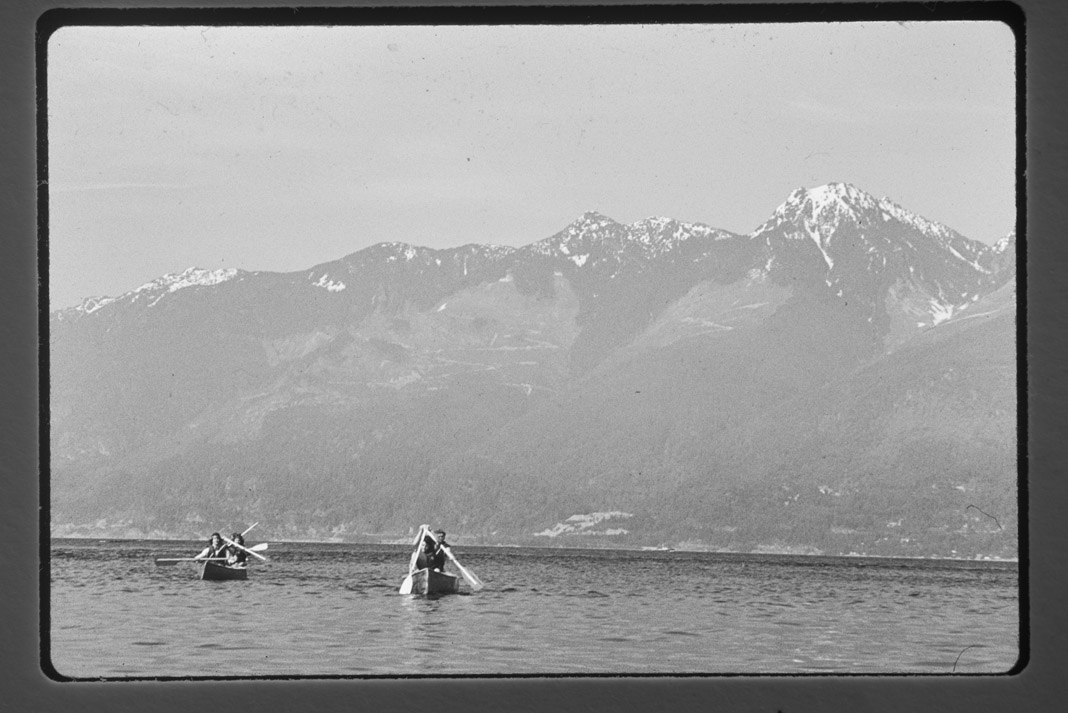 canoes paddling in the distance with mountains in the background