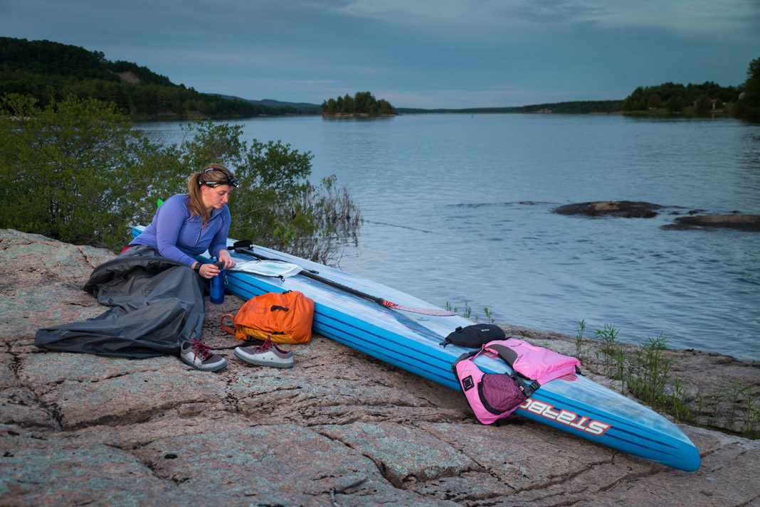 woman surrounded by paddlboarding gear