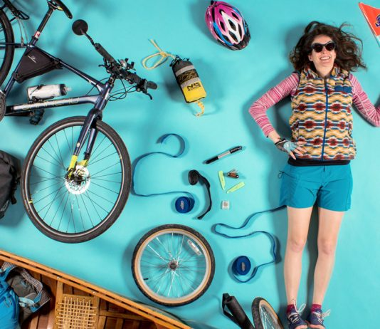 Woman surrounded by things needed for a bike canoe trailer rig
