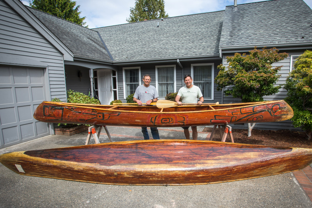 two mend standing behind two canoes