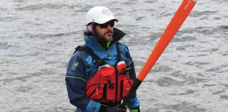 Man holding a paddle wearing paddling gear