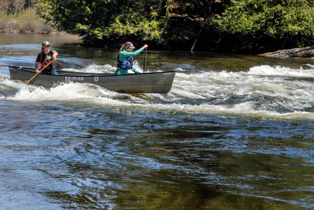 Two women canoeing down a rapid in the H2O Voyageur 17 canoe