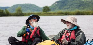 two men in kayaks laughing