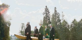 6 men in tuxedos carrying a wooden kayak with an urn