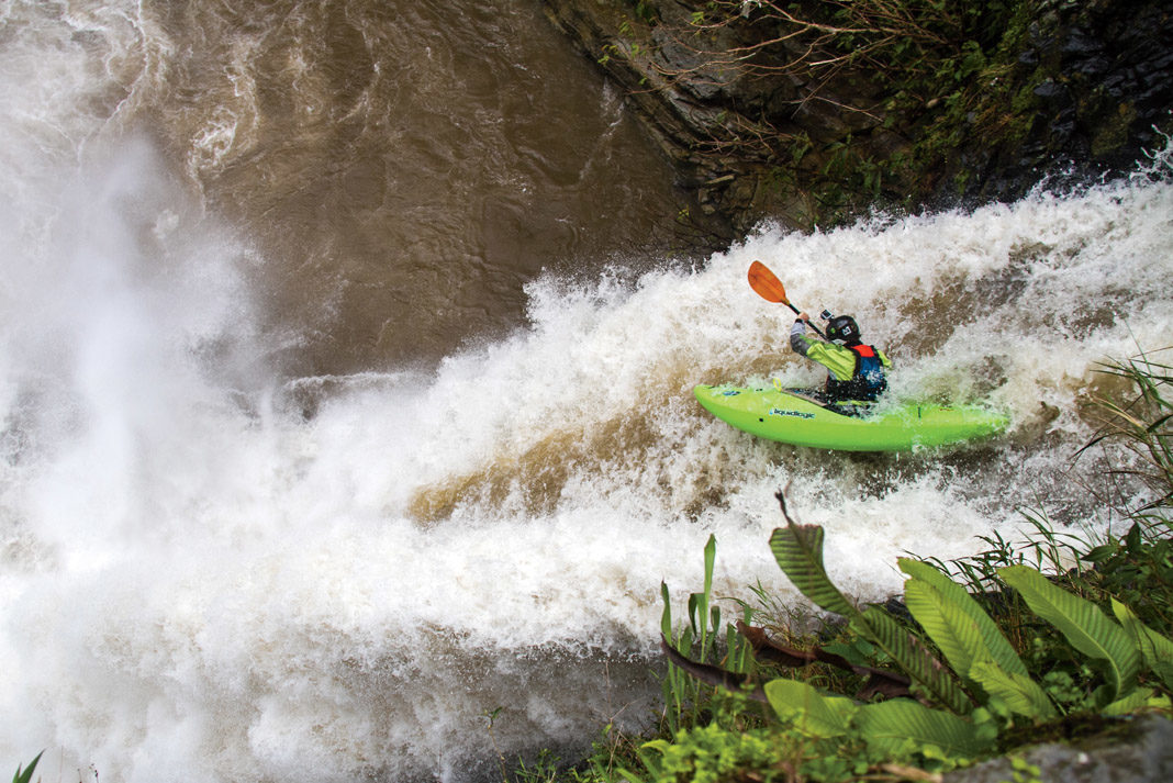 skilled kayaker dropping off a waterfall