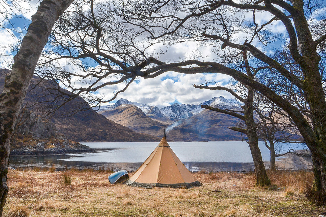 tent and canoe set up side of lake in Scotland