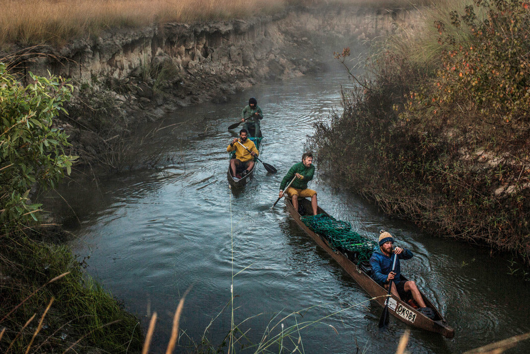 four men in two canoes paddling in Africa