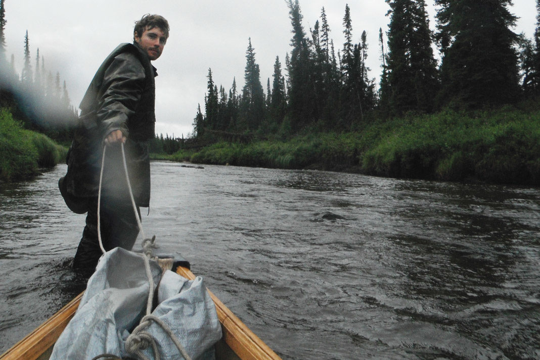 man pulling canoe behind him standing in a river