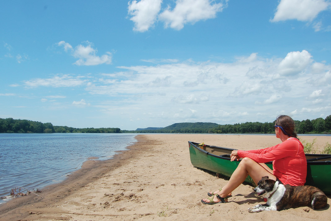 woman takes a break with her dog while canoeing the lower Wisconsin River