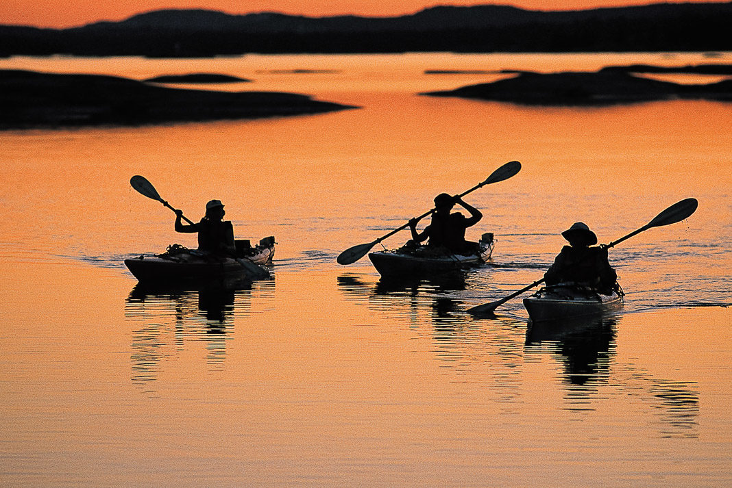 three paddlers kayaking in the sunset light