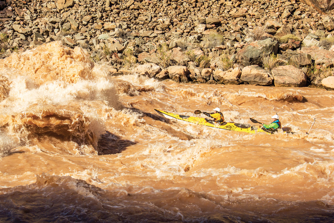 Two people in a tandem kayak going through whitewater