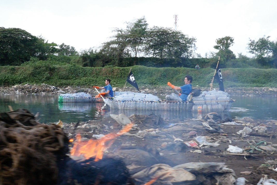 two men in kayaks made out of trash