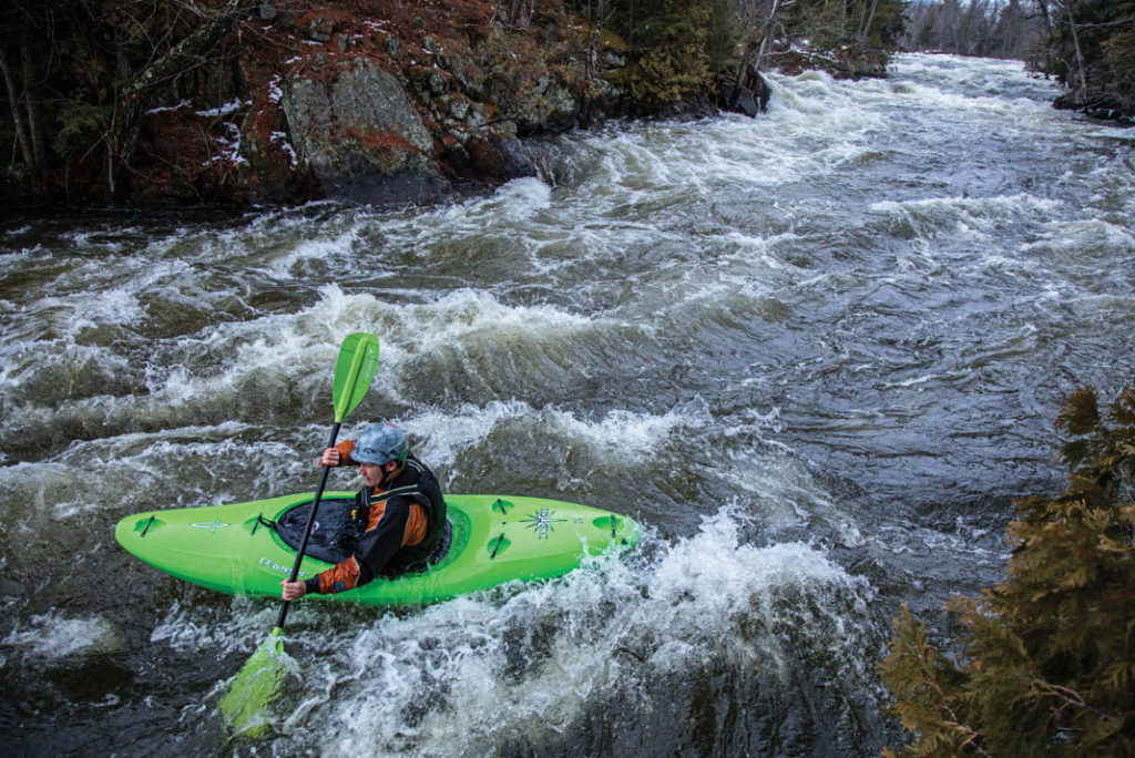 boater in a green kayak paddling through whitewater