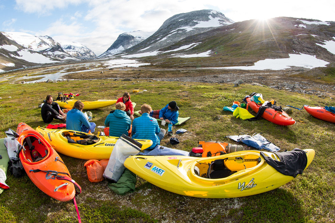 several paddlers surrounded by kayaks with mountains in the background