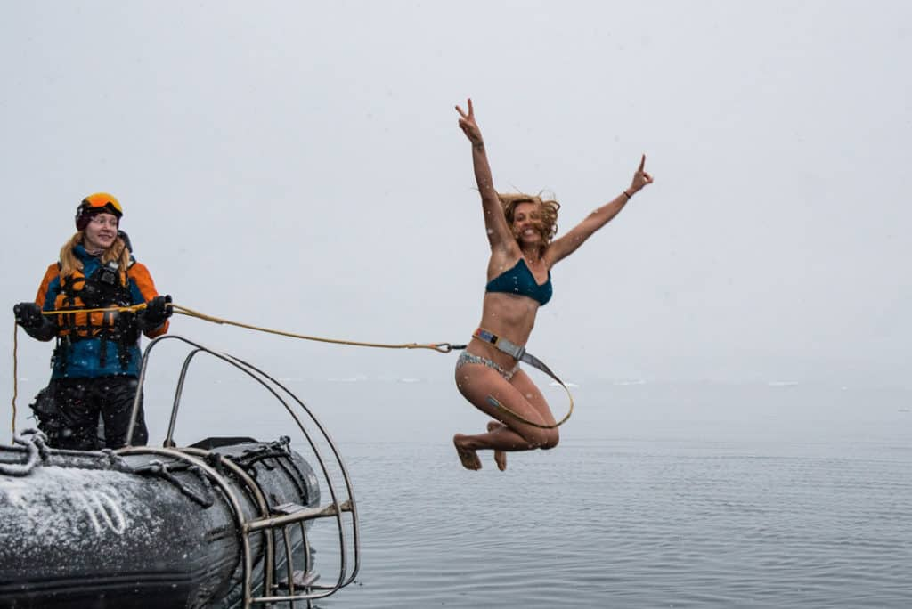 woman jumping into ice cold water with a harness