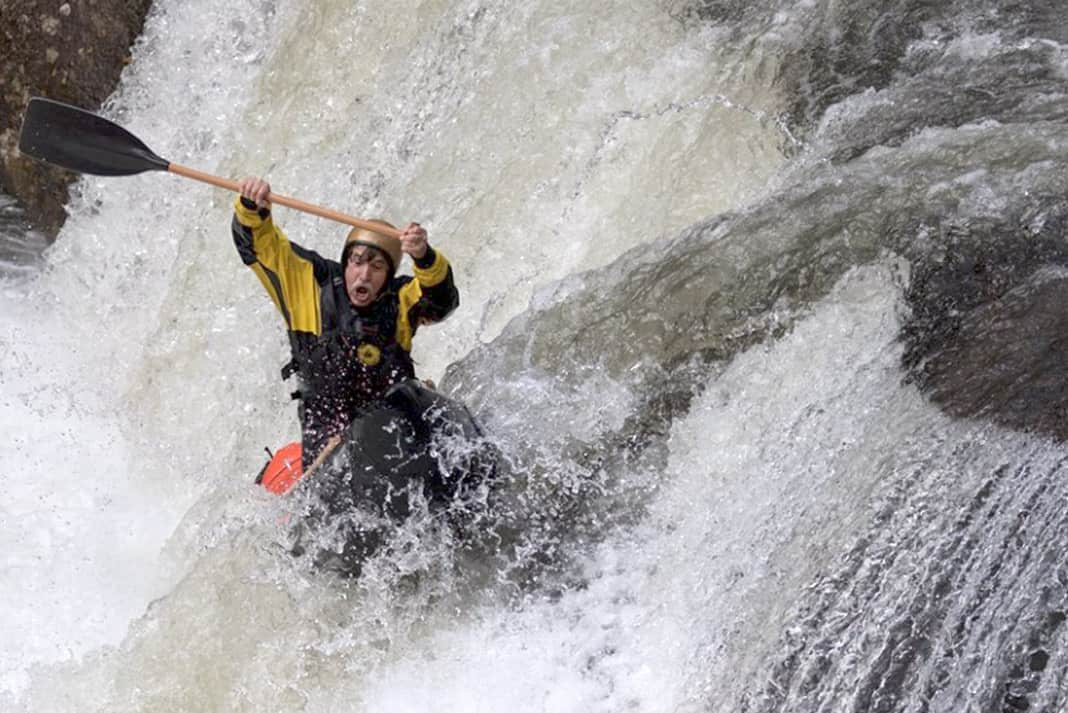 man in a canoe dropping a waterfall
