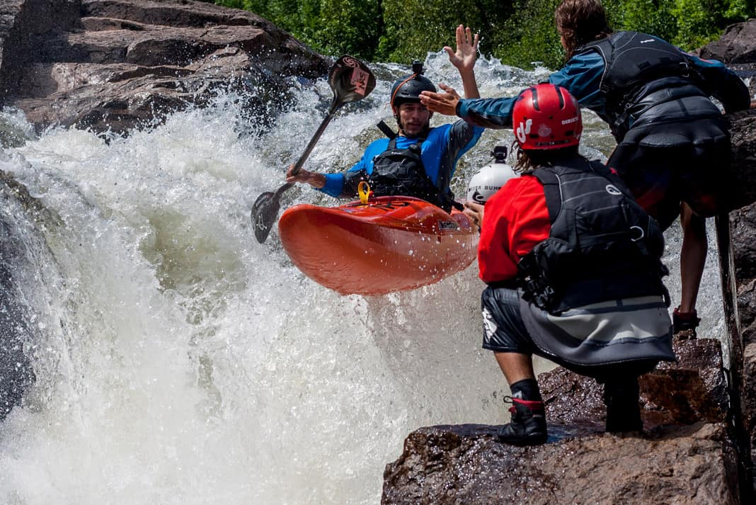 kayaker giving a high five to a friend on shore, all wearing PFDs