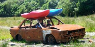 two men in a broken down car with two kayaks strapped to the hood of the car