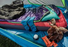 Socks, poncho, sleeping pad, sleeping bag, and other gear laid out on floor of tent