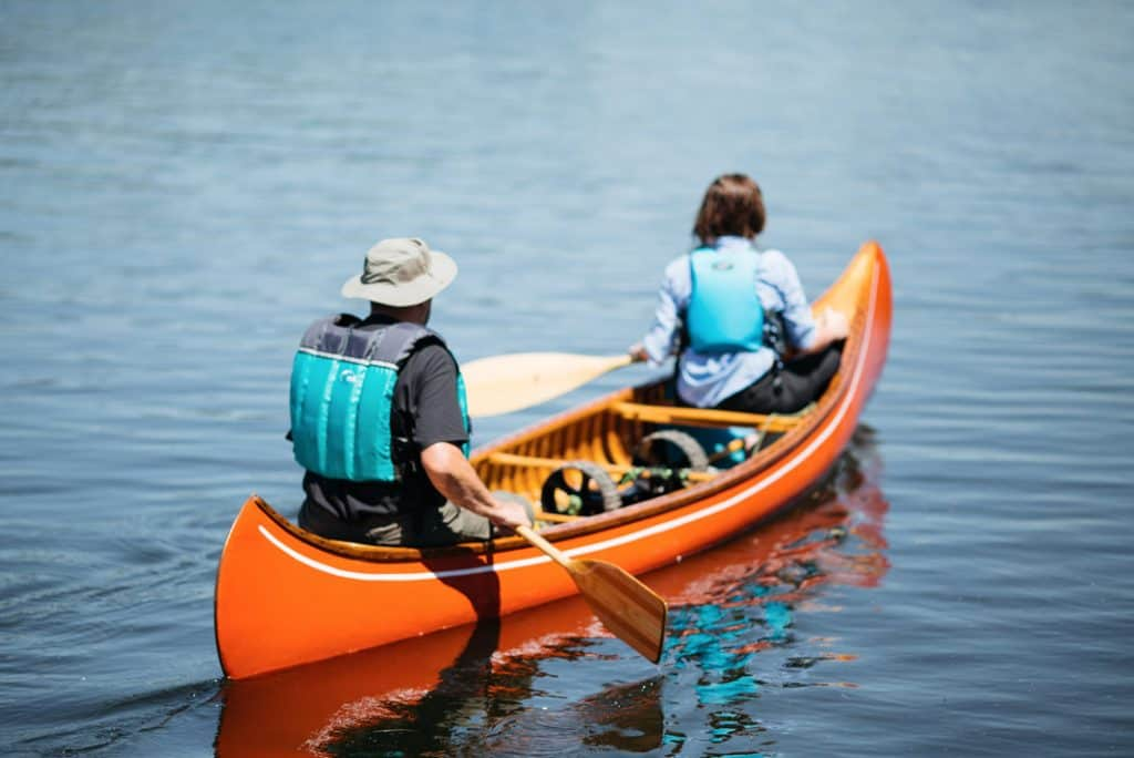 Two people paddling in wooden canoe