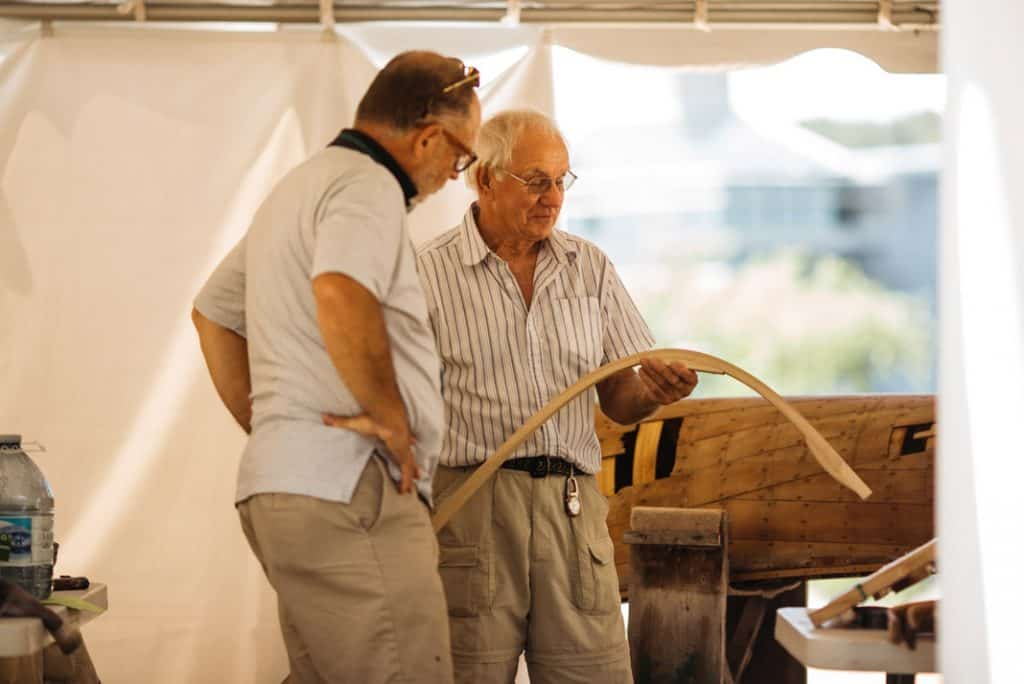 Two gentleman holding a rib to be put into a wooden canoe