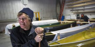 Explorer Will Steger smiling in front of his custom made canoes holding a canoe paddle