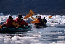 several kayakers paddling Feathercraft kayaks in amongst ice in the Arctic