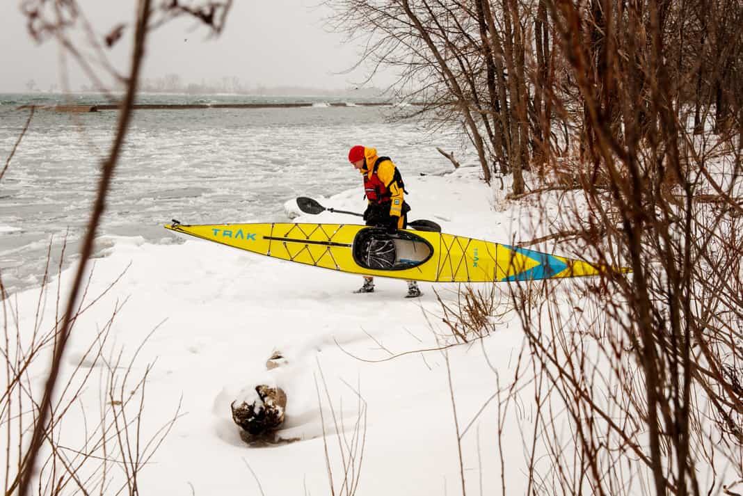 Man walking on snow carrying yellow kayak