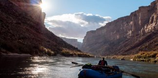 person paddling a raft down a scenic canyon