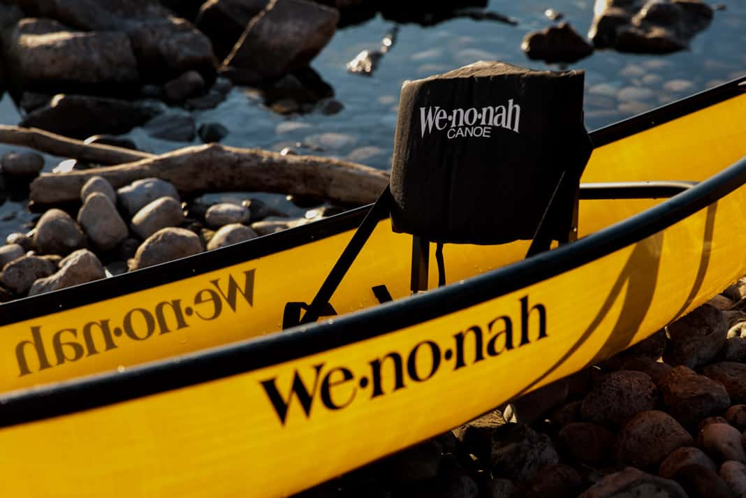 a yellow canoe with Wenonah written on the side
