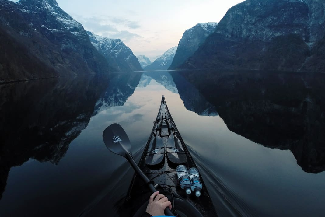 a scenic view of mountains with the bow of a kayak and kayak paddles