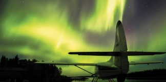 a seaplane docked with green northern lights in the sky