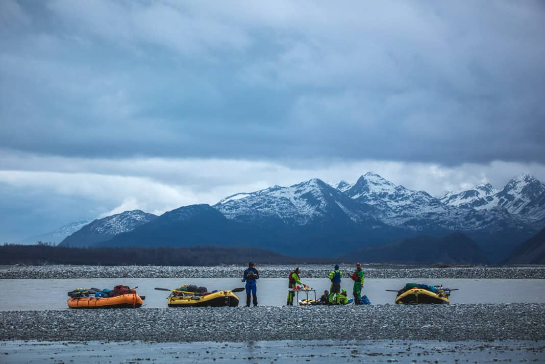 people standing around three rafts with mountains in the background
