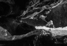 picture taken through an opening in rocks of a kayaker paddling in whitewater