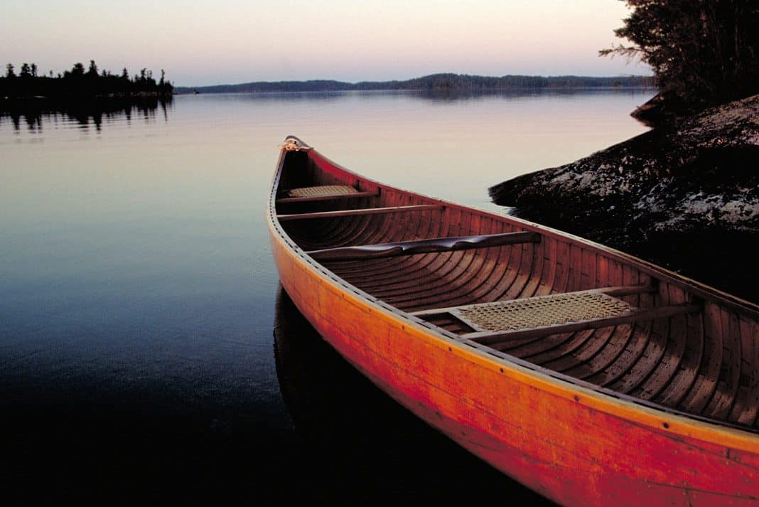 a canoe sitting on a lake ready to be launched