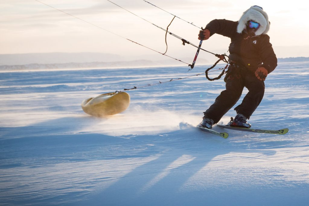 person dragging a kayak behind him while kitskiing on ground covered in snow and ice